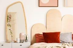 Cuscini rossi sul letto con la testata accanto alla tavola di condimento con la m. Fotografie Stock Libere da Diritti
