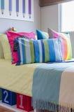 Cuscini variopinti nella camera da letto del bambino a casa immagine stock
