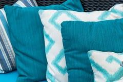 Cuscini variopinti su un sofà blu Bianco, blu, blu scuro immagine stock
