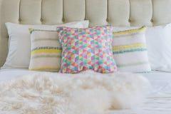 Cuscini variopinti sul letto bianco in camera da letto moderna fotografie stock
