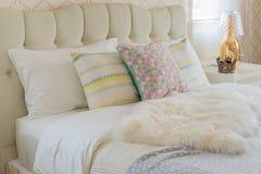 Cuscini variopinti sul letto bianco in camera da letto moderna fotografia stock libera da diritti