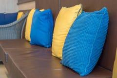 Cuscini variopinti sul salone di cuoio del sofà Fotografia Stock