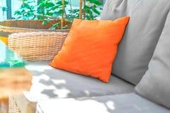 Cuscino arancio sul sofà grigio con il fondo floreale di luce solare sul terrazzo o sul caffè di estate Modello per annunciare fotografie stock