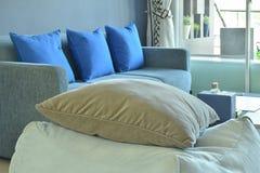 Cuscino di Brown sul panchetto cubico del tessuto beige con il sofà blu Fotografia Stock