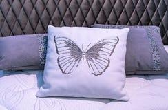 Cuscino di cuoio bianco con la farfalla ricamata nell'interno della camera da letto immagini stock