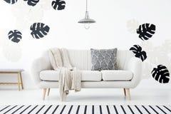 Cuscino e coperta modellati sul sofà in interi bianco del salone Immagini Stock