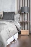 Cuscino grigio sul letto bianco in camera da letto moderna con la lampada nera Immagini Stock Libere da Diritti