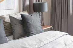 Cuscino grigio sul letto bianco in camera da letto moderna con la lampada nera Fotografie Stock Libere da Diritti