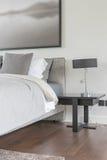 Cuscino grigio sul letto bianco in camera da letto moderna con la lampada nera Fotografia Stock Libera da Diritti
