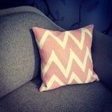 Cuscino rosa che decora un sofà Fotografia Stock