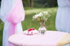 Cuscino rosso degli anelli sulla tavola con i fiori nozze Fotografie Stock Libere da Diritti