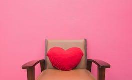 Cuscino rosso del cuore sui precedenti di rosa della parete della sedia Fotografia Stock