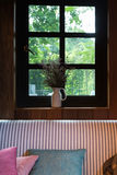 cuscino, sofà e fiore accanto alla finestra Immagini Stock Libere da Diritti