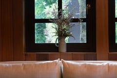 cuscino, sofà e fiore accanto alla finestra Fotografie Stock