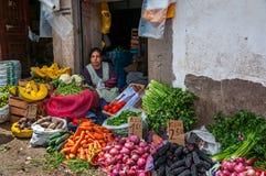 CUSCO, PERÚ - 8 DE OCTUBRE DE 2016: La mujer latinoamericana vende verduras frescas y las frutas en el mercado foto de archivo