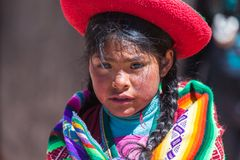 Native of Cusco. Cusco, Peru, July 2018: Native girl from Cusco, with her typical costumes, looks surprised at the photographer while taking pictures royalty free stock photos