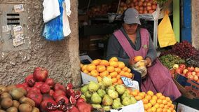 CUSCO, PERU- JUNE 20, 2016: a woman bags fresh mandarins at a market in cuzco