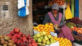 CUSCO, PERU 20 JUNI, 2016: een vrouw doet verse mandarins bij een markt in cuzco in zakken stock afbeelding
