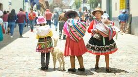 Cusco, Peru - 01 03 2019 Peruviaanse vrouwen en meisje in traditionele kleding en kleine lama op de straat van Cusco, Peru, stock fotografie