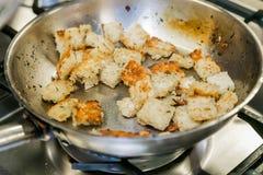 Cuscurrones del pan blanco que fríen en una cacerola de aceite de oliva Imagen de archivo libre de regalías