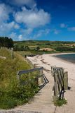 Cushendun beach. Wooden pathway leads down to the sandy beach at Cushendun, County Antrim, Northern Ireland, where a solitary figure sits in the sun stock images