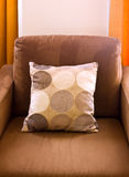 Cushion on chair. A modern cushion on a brown suede effect armchair stock image