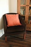 Cushion on a chair. An orange cushion on a brown settee with a bookcase behind it royalty free stock photography