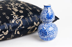 Cushion with chinese characters writing and blue ceramic vase. In a white background Royalty Free Stock Photos