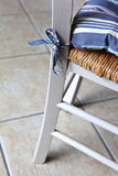 Cushion. Decorative cushion tied on a wicker chair stock photos