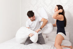Cushion fight. Young couple makes a cushion fight in bed stock photo