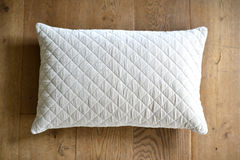 Cushion. Individual textured cushion on a wooden background royalty free stock images