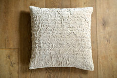 Cushion. Individual textured cushion on a wooden background royalty free stock photography