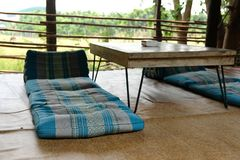 Cushion on mat on patio with rural view. Blue cushion on mat on patio with rural view stock photography