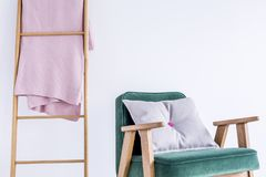 Cushion with pink button. Grey cushion with pink button in the middle on green armchair and ladder with coverlet royalty free stock photography