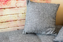 Cushion on the sofa near the wall. Cosy nook - the cushion on the sofa near the bricklike wall Stock Images