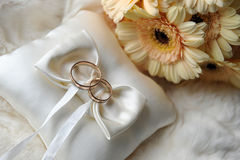 Cushion with wedding rings. Bride bouquet of yellow flowers and cushion with wedding gold rings royalty free stock photos