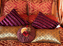 Cushions on bed. Luxurious cushions on bed in gold brocade, purple velvet and red textiles Royalty Free Stock Images