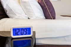 Cushions and dressed bed linen and electronic alarm clock. On the bed in the hotel Stock Images