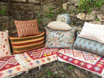 Cushions and kelim on a stone bench Stock Photos