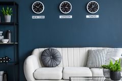 Cushions placed on light grey couch in dark living room interior. With three clocks and plants royalty free stock photos