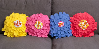 Cushions. Row of colorful home made fleece cushions with a floral pattern royalty free stock photo