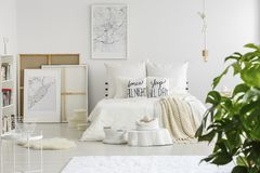 Cushions with text. Placed on a king-size bed with white bedclothes standing in bright room interior with posters and decor stock images