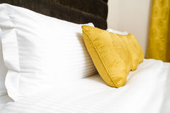 Cushions , Yellow pillows on bed in hotel room Royalty Free Stock Photo
