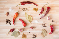 Cusine background. Chili pepper, bay leaf, black pepper, garlic, salt, spices on light wooden background with copyspace. Cusine background stock images
