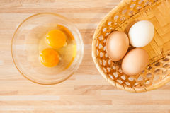 Cusine background. Eggs in braided bucket and raw eggs in glass pialat on light wooden background. Cusine background royalty free stock photos