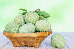 Custard apples with basket on old wooden table Stock Photos