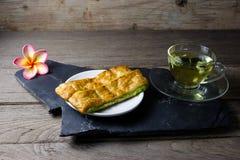Custard bread with chrysanthemum tea on wood background Stock Photos