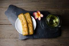 Custard chleb z chryzantemy herbatą na drewnianym tle Obrazy Stock