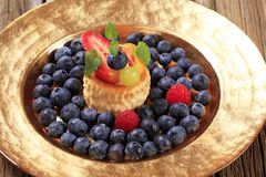 Custard filled vol-au-vent and fresh blueberries Royalty Free Stock Images