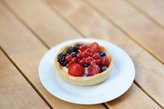 Custard fruit tart on white plate Royalty Free Stock Images